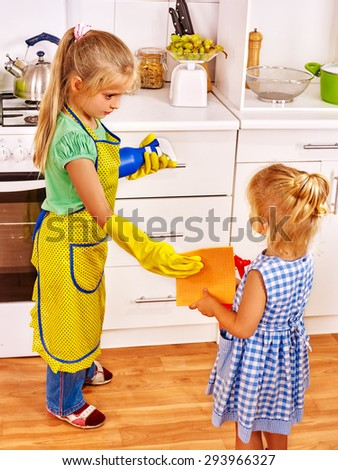 Children sister cleaning  home kitchen. Housekeeping.