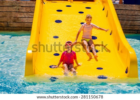 Children sister on water slide at aquapark. Summer holiday. - stock photo