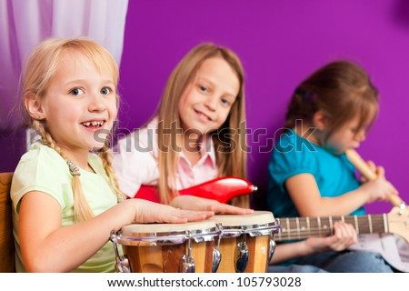 Children - sisters - making music at home, they are practicing playing guitar, bongo and flute as instruments - stock photo