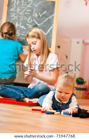 Children � sisters - playing at home; one child is still a baby - stock photo