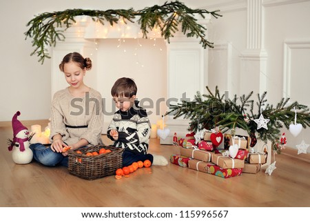 Children sit on the floor. Christmas and many decorations.