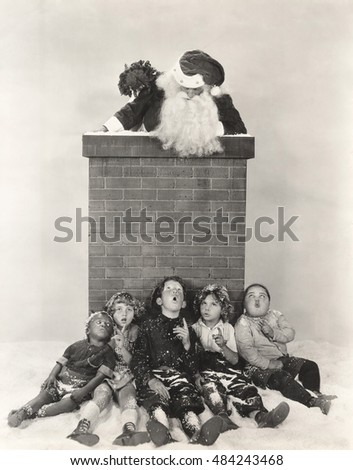 Children sitting against chimney looking at Santa Claus