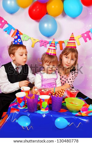 children sitting at the table and celebrating first birthday of baby girl - stock photo