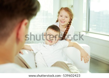 Children sitting at their father at home