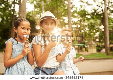 Children sitting on a bench and eating ice-creams - stock photo