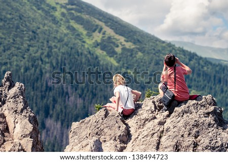Children sitting on mountain peak and looking at green valley