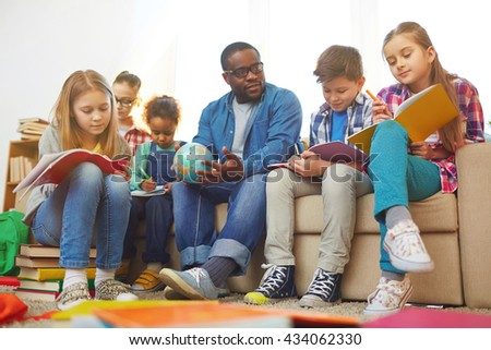 Children sitting on sofa with teacher and writing