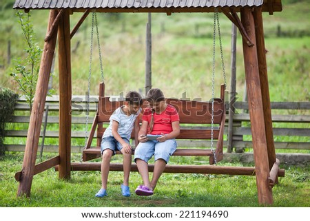 Children sitting on swing with digital tablet - stock photo