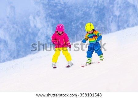 Children skiing in the mountains. Toddler kids in colorful suit and safety helmet learning to ski. Winter sport for family with young child. Kid ski lesson in alpine school. Snow fun for little skier. - stock photo