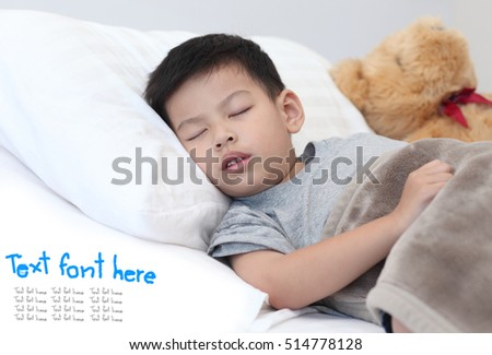 Children sleep on the bedroom,Asian boy sleeping on bedroom.Child sleeping with beardall on the bed.