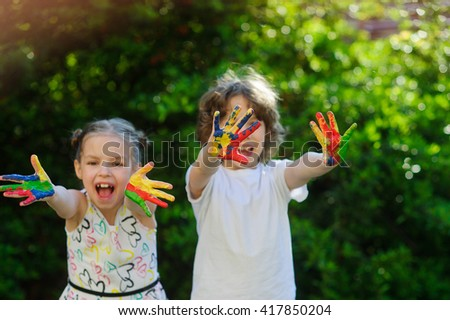 Children soiled with paint, having fun and showing their dirty hands to the camera. Children have fun painting / drawing. Children's creativity. Art for baby. Emotions. Children playing.  - stock photo