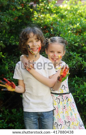 Children soiled with paint, having fun, child shows his dirty hands to the camera. Child has fun painting / drawing. Children's creativity. Art for baby. Emotions. Children playing.  - stock photo
