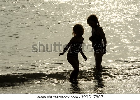 Children splashing in glittering sea