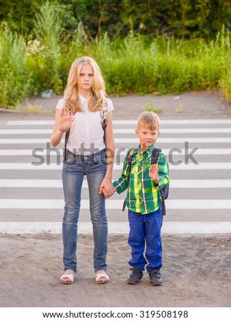Children stand near a pedestrian crossing and show an open palm - stock photo
