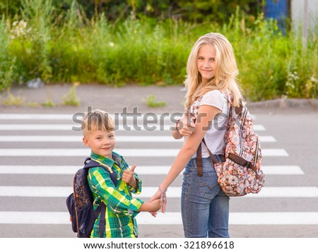 Children stand near a pedestrian crossing and showing thumbs up. - stock photo