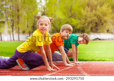 Children stand with bended knee ready to run - stock photo