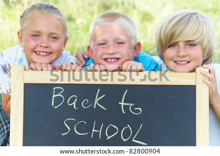 """children standing next to the blackboard with the text """"back to school"""" - stock photo"""