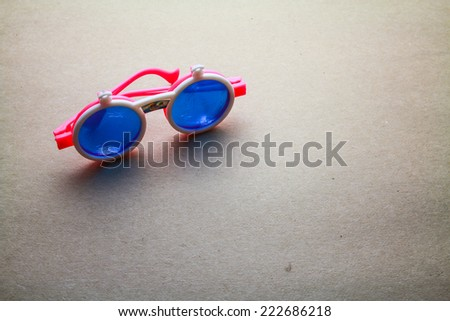 Children sunglasses isolated on seamless brown paper background - stock photo