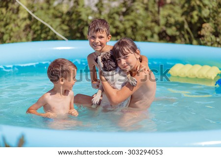 children swim in the pool with the dog