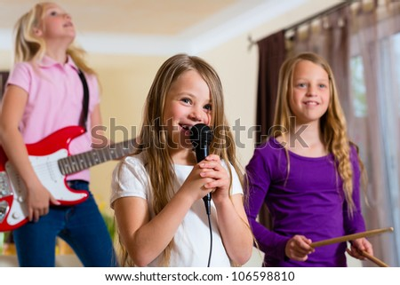 Children - three sisters - playing in a band making music - stock photo