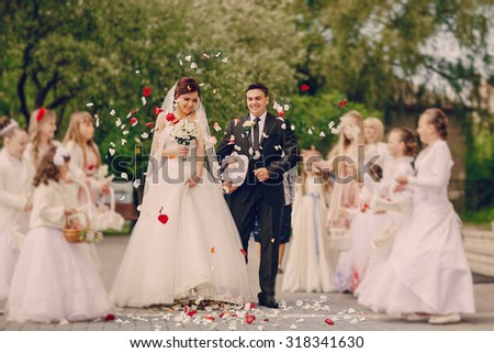 Children throwing petals on the bride at the church, happy moment - stock photo