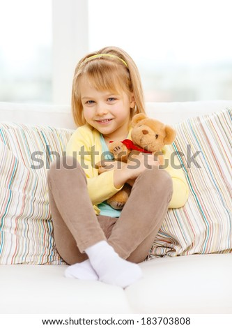 children, toys and happiness concept - smiling little girl with teddy bear sitting on sofa at home