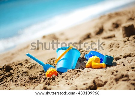 Children toys: bucket, shovel, molds lie on the sand on the seashore. - stock photo