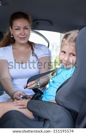 Children transportation with baby car seat. Caucasian family in vehicle - stock photo