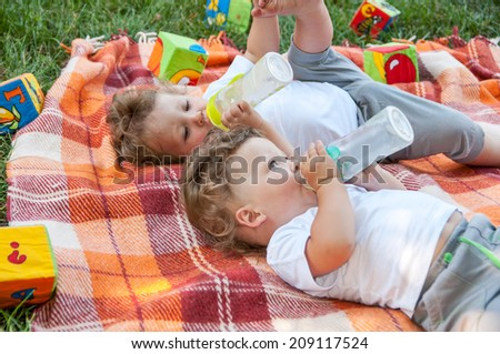 children twins lay on the coverlet among the toys and drink water from a bottle - stock photo