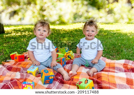 children twins sitting on a blanket among the toys in nature - stock photo