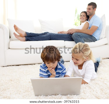 Children using a laptop on floor and parents lying on sofa - stock photo