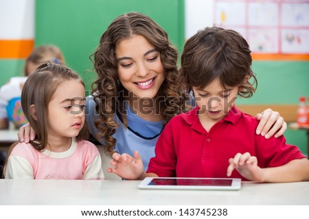 Children using digital tablet with teacher at classroom desk - stock photo