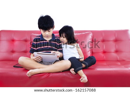 Children using electronic tablet together sitting on the red sofa