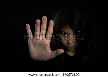 Children violence. Girl with her hand extended signaling to stop. - stock photo