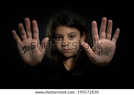 Children violence. Stop now are write on extended girl's hands. - stock photo