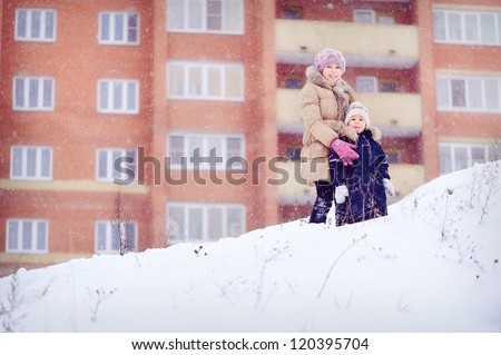 Children walk in nature. Boy and girl on a high mountain. Lots of snow. Winter and cold. Portrait of children. Sister hugging brother. - stock photo