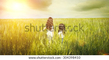 Children walking in wheat field - stock photo