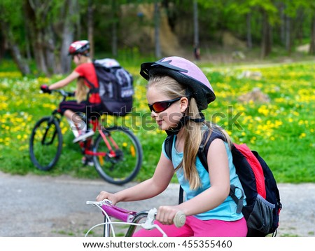 Children wearing bicycle helmet and glasses with rucksack rides bicycle. Bicyclist children is looking forwaqrd. Children ride on green grass and flowers in park outdoor. - stock photo