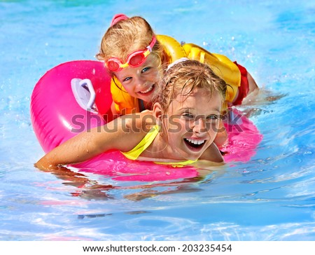 Children wearing life jacket in swimming pool. - stock photo