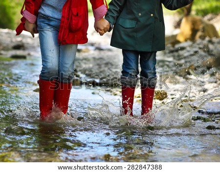 Children wearing rain boots jumping into a mountain river. Close up - stock photo