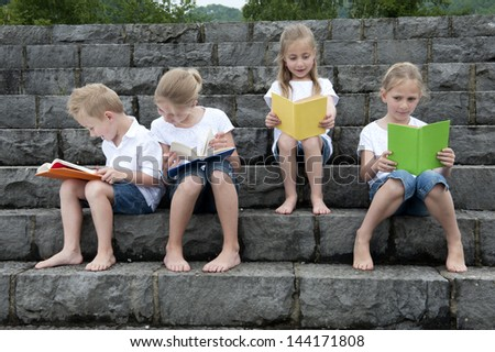 children with a book seated outdoors on stairs - stock photo