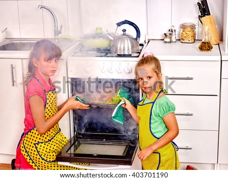 Children with a burnt cooking chicken in the kitchen. Smoke. Faces of the children smeared with soot.