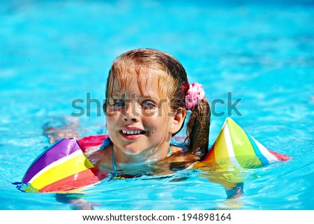 Children with armbands in swimming pool. - stock photo