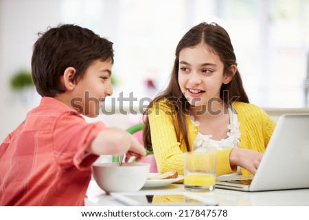 Children With Digital Tablet And Laptop At Breakfast - stock photo