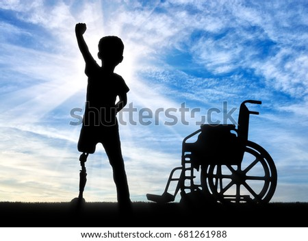 Children with disabilities concept. Happy disabled boy with a prosthetic leg standing near a wheelchair against the sky
