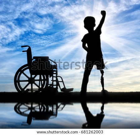 Children with disabilities concept. Happy disabled boy with a prosthetic leg standing near a wheelchair at the river with reflection