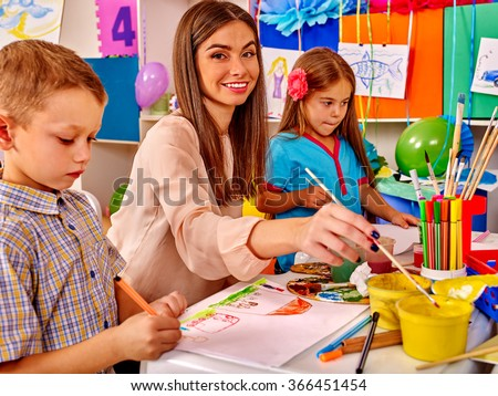 Children with female teacher painting on paper by paint and pencils  in  kindergarten .  - stock photo