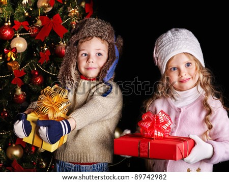 Children with gift box near Christmas tree. Outdoor.