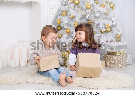children with gifts under the Christmas tree