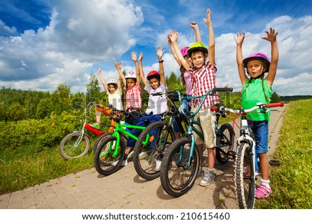Children with helmets sit on their bikes in a row - stock photo